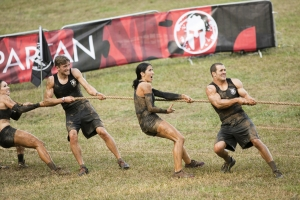 """SPARTAN: ULTIMATE TEAM CHALLENGE -- Episode 101 -- Pictured: (l-r) Maggie Thorne, Spencer Mahoney, Monica Gillmore, Lance Pekus of """"Team GRIT"""" on the Herc Hoist -- (Photo by: Mark Hill/NBC)"""